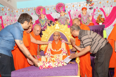 Sants and disciples present a shawl of flowers and seeds to His Divine Holiness Acharya Swamishree