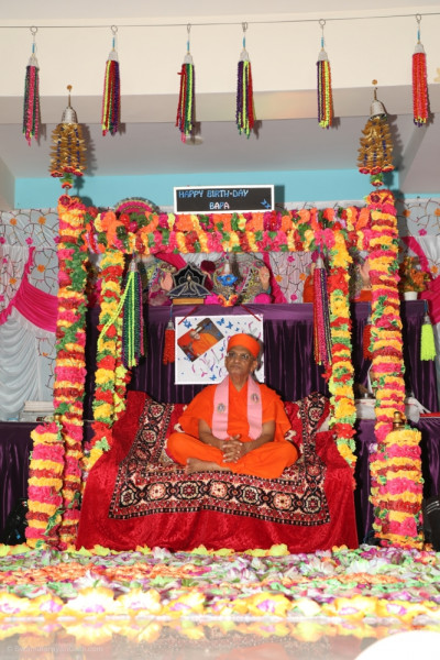 Divine darshan of Acharya Swamishree seated on the charming swing