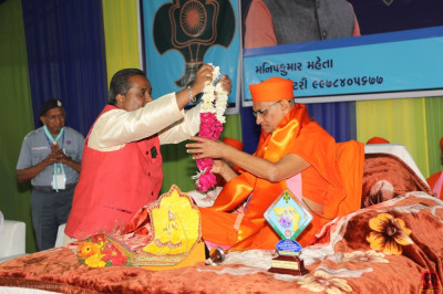 Organisers present garlands of flowers to His Divine Holiness Acharya Swamishree