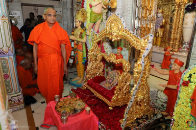 Divine darshan of Acharya Swamishree gently swinging Shree Harikrishna Maharaj