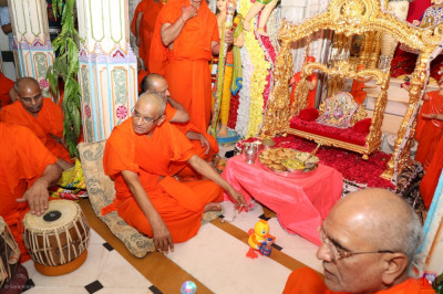 His Divine Holiness Acharya Swamishree gently swings Shree Harikrishna Maharaj