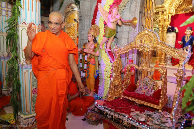 Divine darshan of His Divine Holiness Acharya Swamishree gently swinging Shree Harikrishna Maharaj