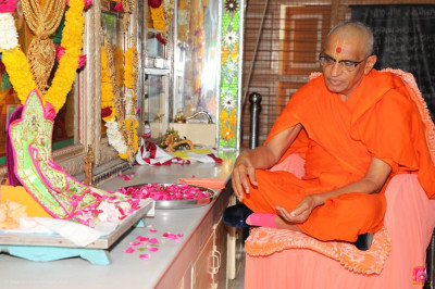 His Divine Holiness Acharya Swamishree showers rose petals at the divine lotus feet of the Lord as part of the anniversary poojan ceremony