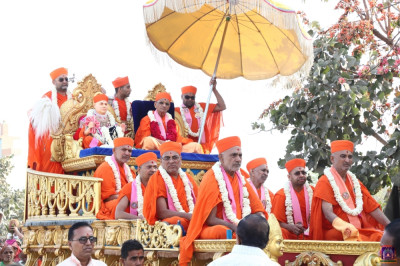 Jeevanpran Swamibapa, Acharya Swamishree Maharaj, and sants give darshan on a chariot during a procession in Vaghjipur