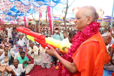 Acharya Swamishree Maharaj showers prasad water on disciples