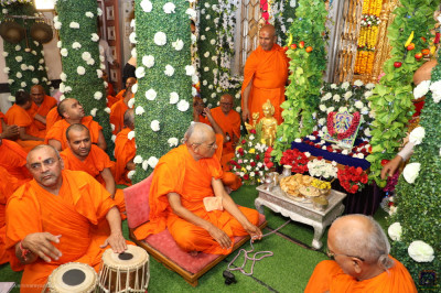Sants perform devotional songs as His Divine Holiness Acharya Swamishree Maharaj gently swings Lord Shree Swaminarayan seated on the swing