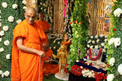 His Divine Holiness Acharya Swamishree Maharaj gently swings Shree Harikrishna Maharaj