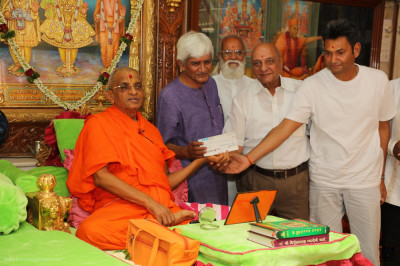His Divine Holiness Acharya Swamishree Maharaj and disciples present a cheque to the hospital representative
