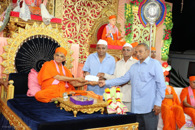 His Divine Holiness Acharya Swamishree Maharaj presents donations for the provision of food for cows