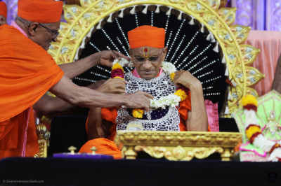 Sants present a garland of flowers to His Divine Holiness Acharya Swamishree Maharaj