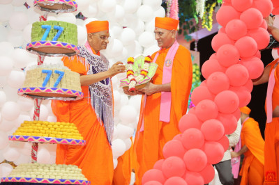His Divine Holiness Acharya Swamishree Maharaj offers the sweet to Shree Harikrishna Maharaj