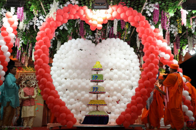 The magnificent five-tier cake made from mountains of different Indian sweets sits at the centre of two gigantic hearts made with red and white balloons