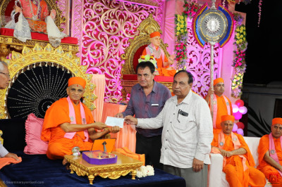 His Divine Holiness Acharya Swamishree Maharaj presents a donation for food for cows