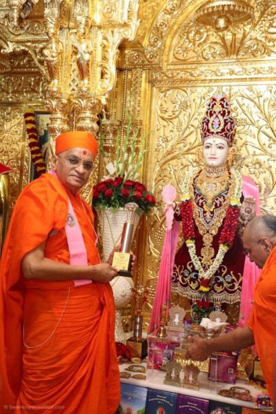 Divine darshan of Acharya Swamishree Maharaj with the trophies to be presented to the winning teams of the devotional evening drama performances