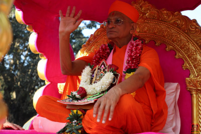 His Divine Holiness Acharya Swamishree Maharaj blesses sants, disciples and local residents, seated on the golden chariot during the morning procession
