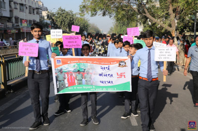 Young disciples dressed in uniform hold placards with messages of peace and patriotism and take part in the procession to the grand assembly