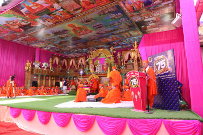 Acharya Swamishree Maharaj and sants seated on the magnificent grand festival stage featuring ceiling art detailing the darshan of the glorious history of Naad Vansh Guruparampara