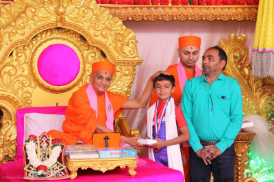 His Divine Holiness Acharya Swamishree Maharaj blesses 8 year old multiple medal-winning Yoga student Namrakumar Parimal Patel with a medal and a prasad shawl