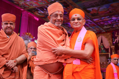 His Divine Holiness Acharya Swamishree Maharaj lovingly embraces Shree Hariprasadji Maharaj on stage