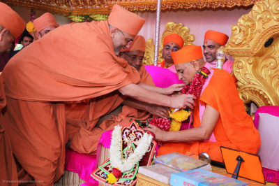 Shree Hariprasadji Maharaj and sants present His Divine Holiness Acharya Swamishree Maharaj with a garland of fresh flowers