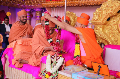 His Divine Holiness Acharya Swamishree Maharaj presents a garland of flowers to the honoured guest of the day, Swamishree Hariprasadji Maharaj of the Haridham Sokhda Akshar Purushottam Sansthan