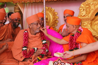 His Divine Holiness Acharya Swamishree Maharaj offers prasad sweets to Hariprasdji Maharaj