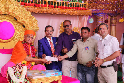Shree Swaminarayan Gadi Sansthan presents a cheque to Shree Swaminarayan Prarthmik Shala trust