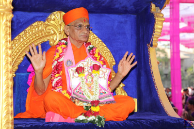 Acharya Swamishree Maharaj showers His blessings on all as the golden chariot enters the grand assembly