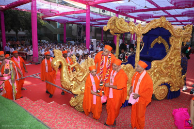 Sants carry His Divine Holiness Acharya Swamishree Maharaj from the golden chariot onto the grand stage