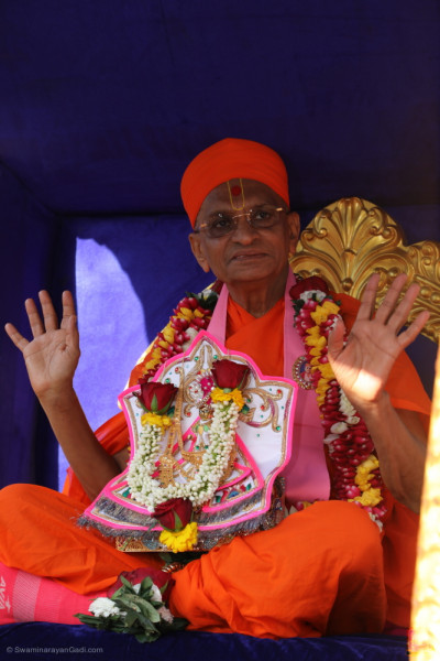 His Divine Holiness Acharya Swamishree Maharaj blesses all seated upon the hand drawn golden chariot