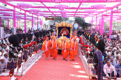 Sants pull the golden chariot into the grand assembly as Shree Muktajeevan Swamibapa Pipe Band Maninagar perform