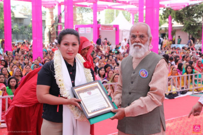 Ms. Arcie D. Fabon presents an award to Shree Swaminarayan Gadi Sanshtan
