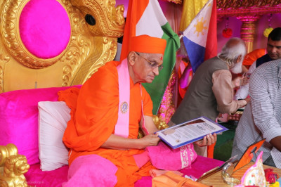 His Divine Holiness Acharya Swamishree Maharaj reading the award presented by the president of PARDSS International Inc