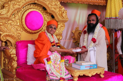 His Divine Holiness Acharya Swamishree Maharaj presents Shree Akhileshwar Maharaj with a prasad shawl, a garland of flowers and prasad