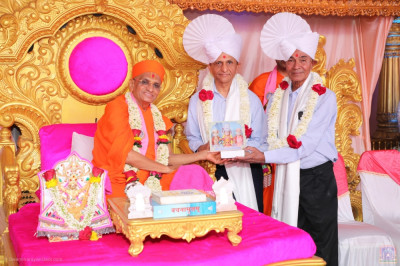 His Divine Holiness Acharya Swamishree Maharaj presents memento to guests