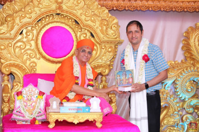 His Divine Holiness Acharya Swamishree Maharaj presents memento to a guest