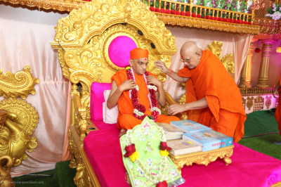 A sant garlands Acharya Swamishree Maharaj on behalf of all sants and disciples taking part in the maha poojan ceremony