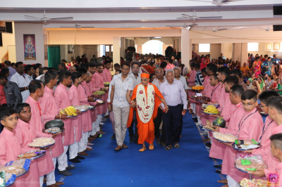 Disciples escort His Divine Holiness Acharya Swamishree Maharaj into the mandir as disciples line on both sides holding gifts for the Lord