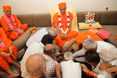 Disciples bath the divine lotus feet of His Divine Holiness Acharya Swamishree Maharaj in the five nectars