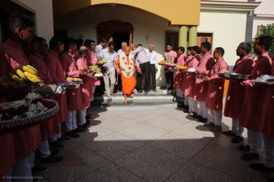 Disciples escort His Divine Holiness Acharya Swamishree as disciples dressed in pink and white hold gifts for the Lord