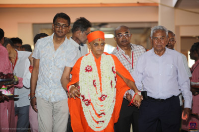 Disciples escort His Divine Holiness Acharya Swamishree Maharaj towards the grand assembly stage