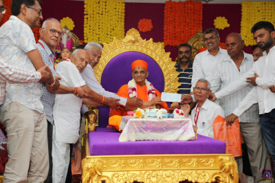 His Divine Holiness Acharya Swamishree Maharaj and disciples present a donation to local charitable organisations