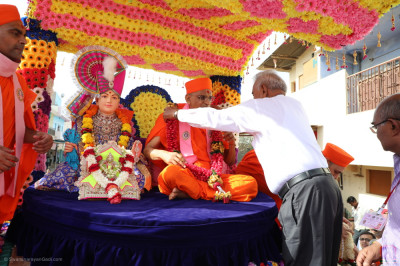 Disciples present a garland of flowers to His Divine Holiness Acharya Swamishree Maharaj