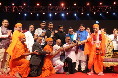 Third place is awarded to disciples from London.  His Divine Holiness Acharya Swamishree Maharaj presents the trophy.