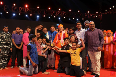First place goes to disciples from Vadodara.  His Divine Holiness Acharya Swamishree Maharaj presents the trophy on stage.