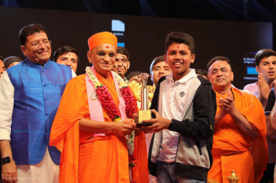 His Divine Holiness Acharya Swamishree Maharaj presents a special award to the best actor of the evening performances to a disciple from Vadodara.