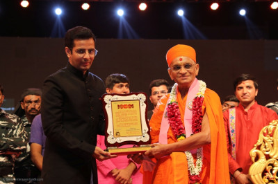 His Divine Holiness Acharya Swamishree Maharaj presents the award to each judge