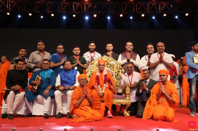 His Divine Holiness Acharya Swamishree Maharaj presents a medal to each disciple from London who took part in the drama performances