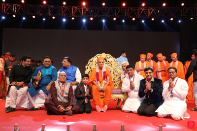 His Divine Holiness Acharya Swamishree Maharaj presents a medal to each disciple from Maninagar who took part in the drama performances