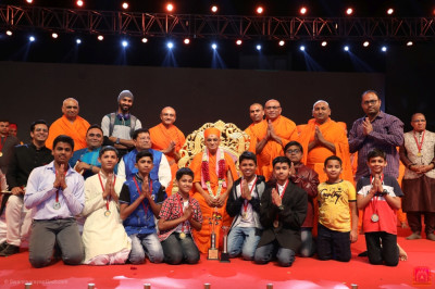 His Divine Holiness Acharya Swamishree Maharaj presents a medal to each disciple from Vadodara who took part in the drama performances